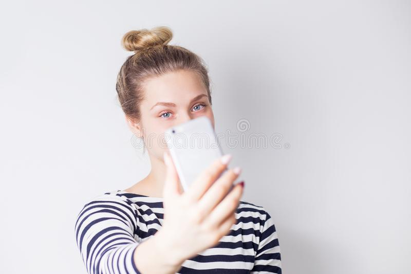 Close-upportret van het mooie aantrekkelijke het glimlachen blondevrouw nemen selfie op smartphone op wit royalty-vrije stock foto
