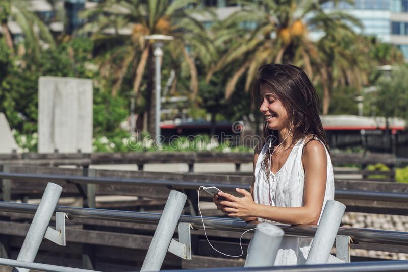 Close-upportret van het vrolijke jonge vrouw luisteren aan de muziek op de telefoon stock afbeelding