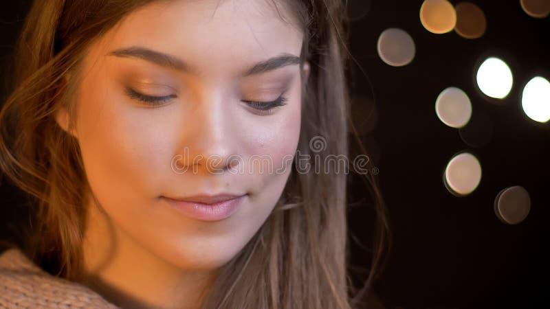 Close-upportret van jong charmant Kaukasisch wijfje die met vreugde en geluk glimlachen die verleidelijk met bokehachtergrond zij royalty-vrije stock afbeelding