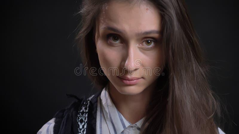 Close-upportret van jong leuk Kaukasisch vrouwelijk gezicht met bruine ogen en donkerbruin haar die recht camera bekijken met stock foto's