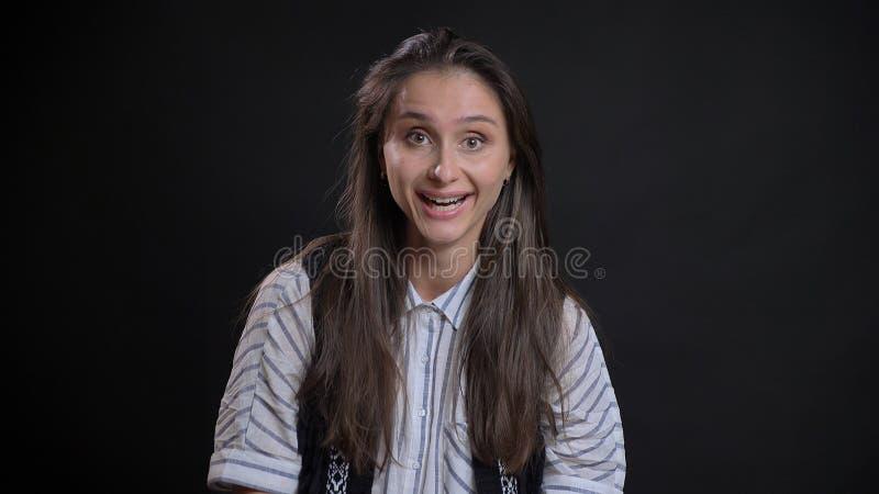 Close-upportret van jong leuk Kaukasisch wijfje met donkerbruin opgewekt en haar die gelukkig terwijl het kijken worden glimlache royalty-vrije stock afbeeldingen