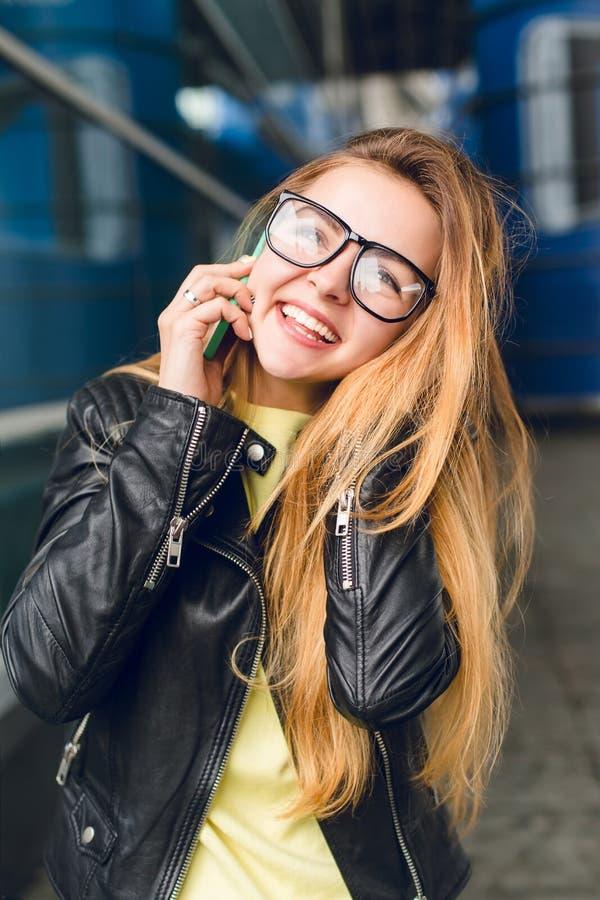Close-upportret van jong meisje met lang haar in glazen buiten in luchthaven Zij draagt zwart jasje, sprekend op telefoon stock afbeeldingen