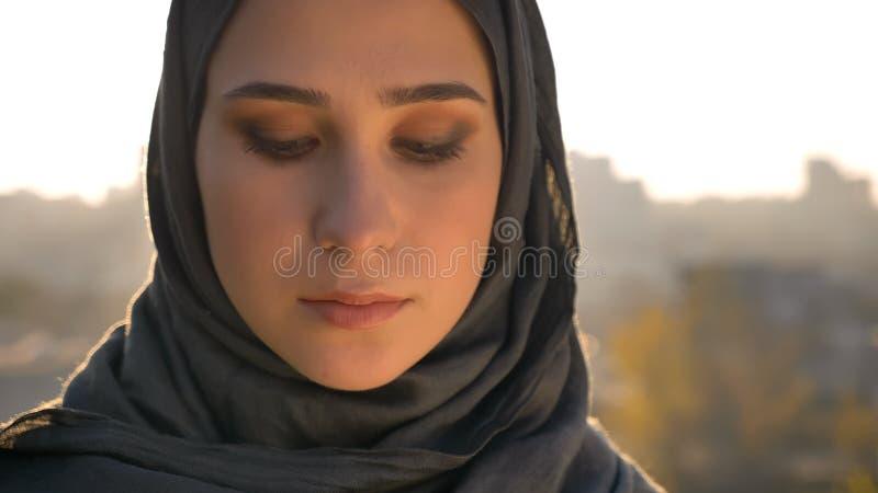 Close-upportret van jong mooi Arabisch wijfje die in hijab neer met het stedelijke plaatsen op de achtergrond kijken royalty-vrije stock foto's
