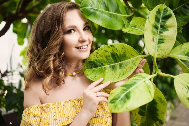 Close-upportret van jong mooi meisje met de krullende kleding van de haarzomer in tropisch bos stock afbeeldingen