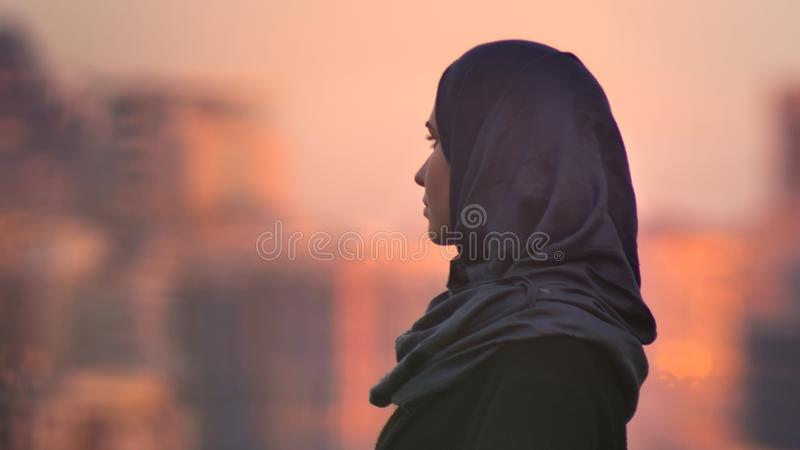 Close-upportret van jong mooi wijfje die in hijab vooruit met stedelijke plaatsende en glanzende gebouwen op kijken royalty-vrije stock afbeelding