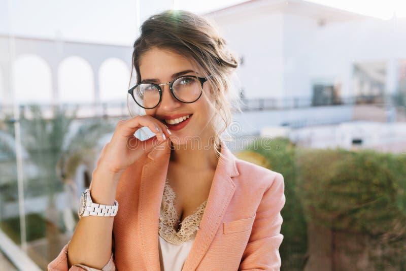 Close-upportret van jong schitterend meisje in modieuze glazen, mooie student die, bedrijfsvrouw elegent roze jasje dragen royalty-vrije stock foto