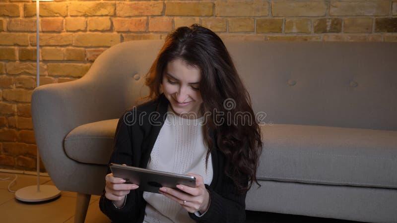 Close-upportret van jong vrij Kaukasisch wijfje die op de tablet in een comfortabel huis binnen met gezichts glimlachen doorblade stock foto's