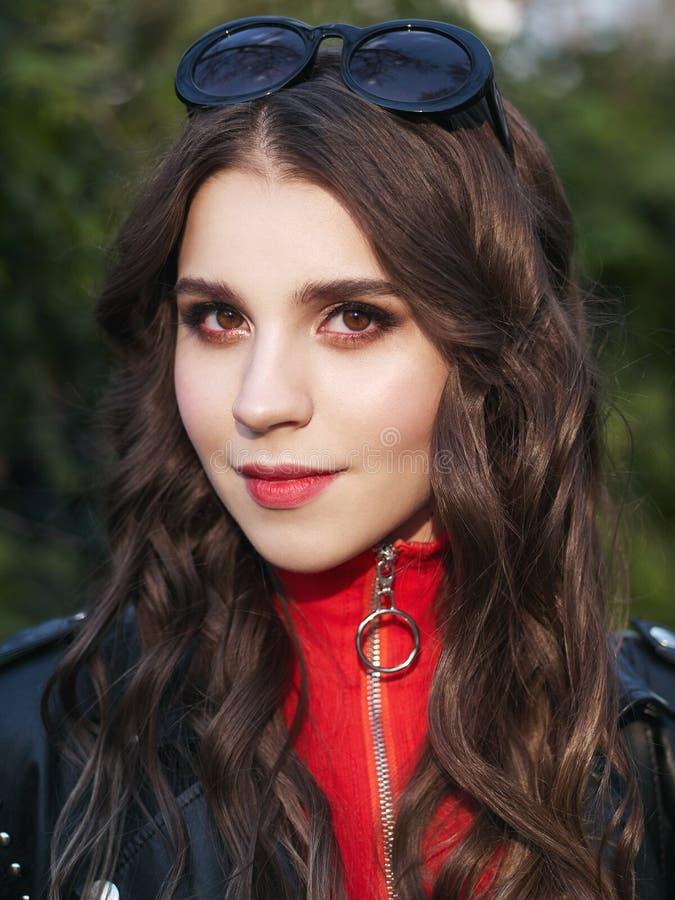Close-upportret van jonge bruin-haired krullende vrouw met het in creatieve rode make-up stellen in openlucht in helder zonlicht  royalty-vrije stock foto