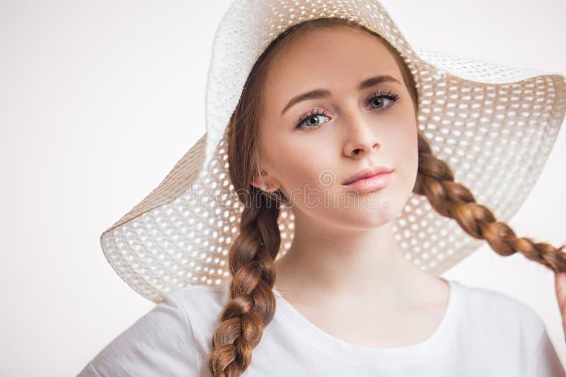 Close-upportret van jonge charmante vrouw in beige hoed en t-shirt die camera op wit bekijken stock fotografie