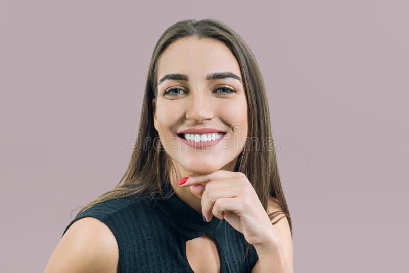 Close-upportret van jonge glimlachende vrouw, het Kaukasische vrouwelijke gezicht van ` s op beige roze pastelkleurachtergrond royalty-vrije stock afbeelding