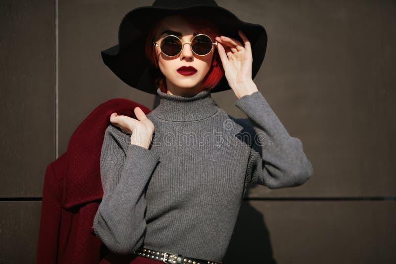 Close-upportret van jonge mooie modieuze vrouw met zonnebril Dame het stellen op donkere grijze achtergrond model royalty-vrije stock foto's
