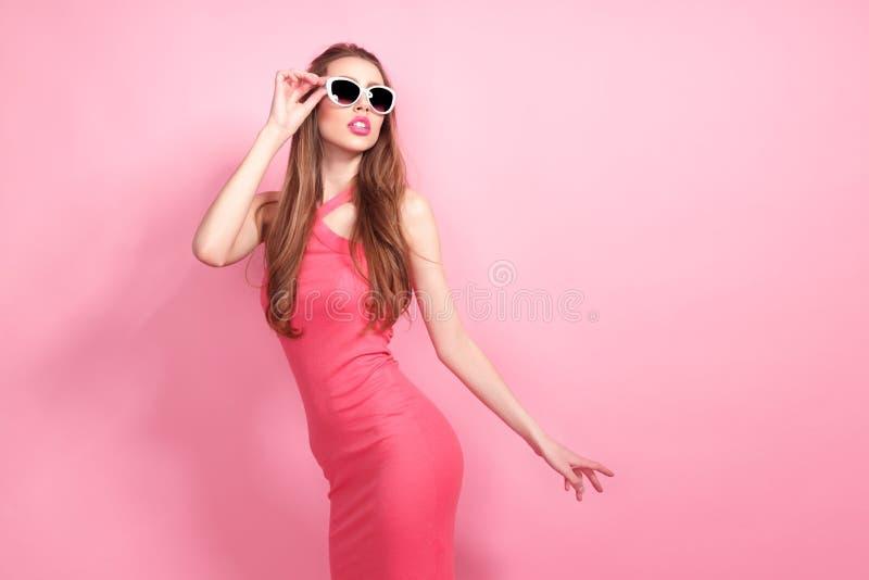Close-upportret van jonge mooie slanke sexy jonge vrouw in sexy kleding met rode sensuele lippen op roze achtergrond in royalty-vrije stock foto