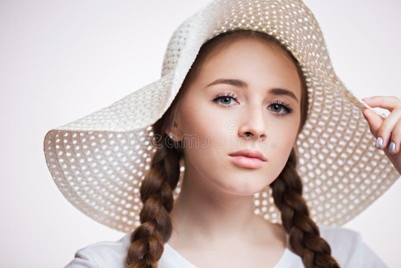 Close-upportret van jonge mooie vrouw die een hoed dragen en de camera op witte achtergrond onderzoeken Meisje met lange wimpers stock afbeelding
