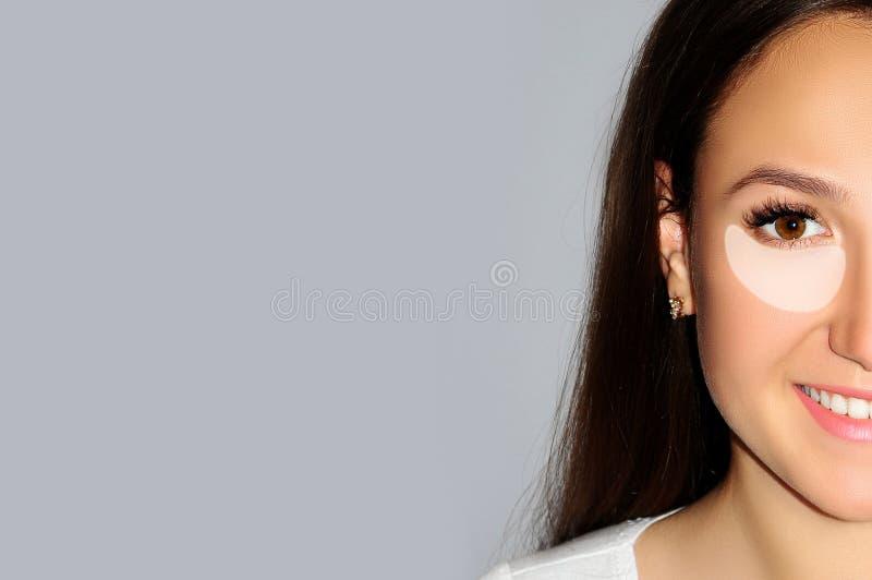 Close-upportret van jonge mooie vrouw met onderstreepte oogcontour, gebied van zwart oog en eerste mimische rimpel Concept gezich stock afbeelding