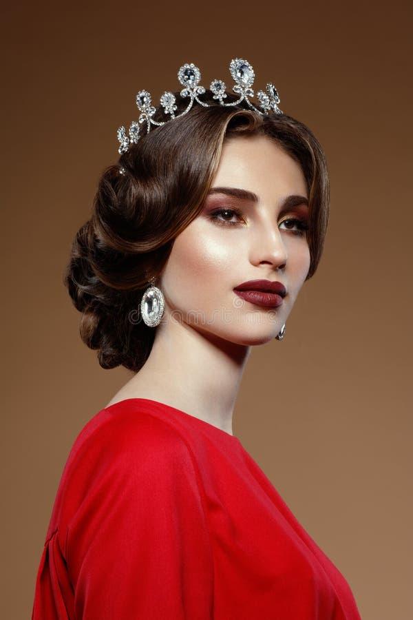 Close-upportret van jonge vrouw, diamantkroon en oorring Donkerbruine schitterende vrouw, op een beige achtergrond stock foto's