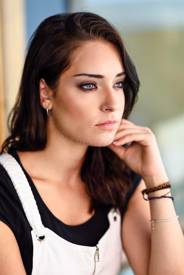 Close-upportret van jonge vrouw met blauwe ogen in openlucht royalty-vrije stock afbeelding