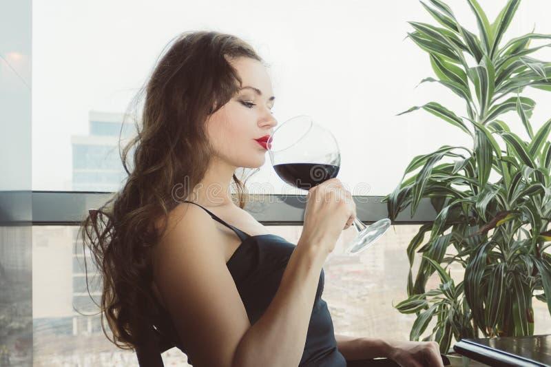 Close-upportret van jonge vrouwelijke klant die rode wijn met gesloten ogen drinken Vrouw het drinken wijn, die een SLOKJE van a  royalty-vrije stock foto's