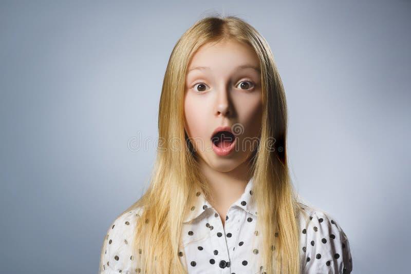 Close-upportret van knap meisje met verbaasde uitdrukking terwijl status tegen grijze achtergrond royalty-vrije stock fotografie