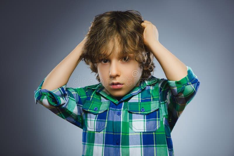 Close-upportret van knappe jongen met verbaasde uitdrukking op grijze achtergrond stock afbeeldingen