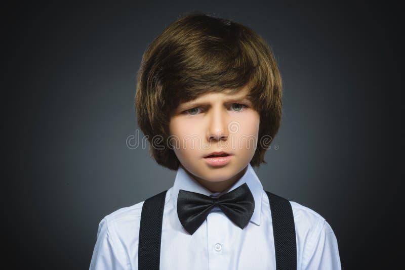 Close-upportret van knappe jongen met verbaasde uitdrukking terwijl status tegen grijze achtergrond royalty-vrije stock foto