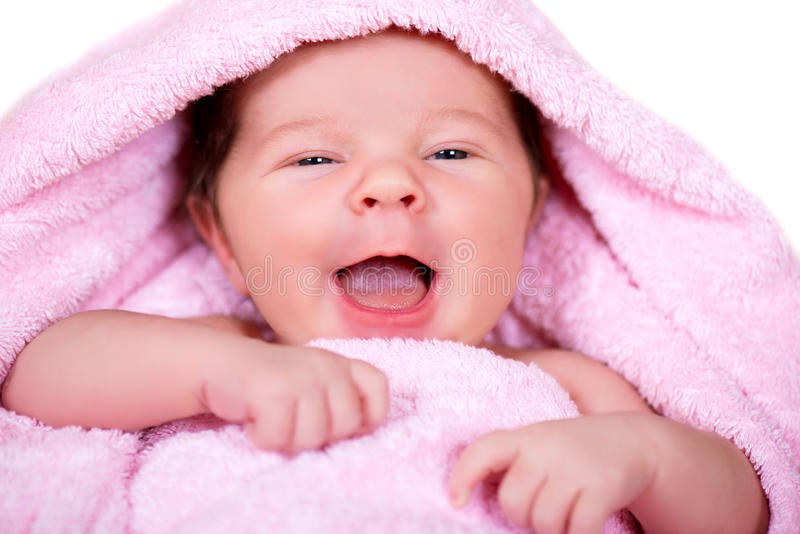Close-upportret van lachende glimlachende pasgeboren baby op roze een badstof-doek handdoek stock foto's