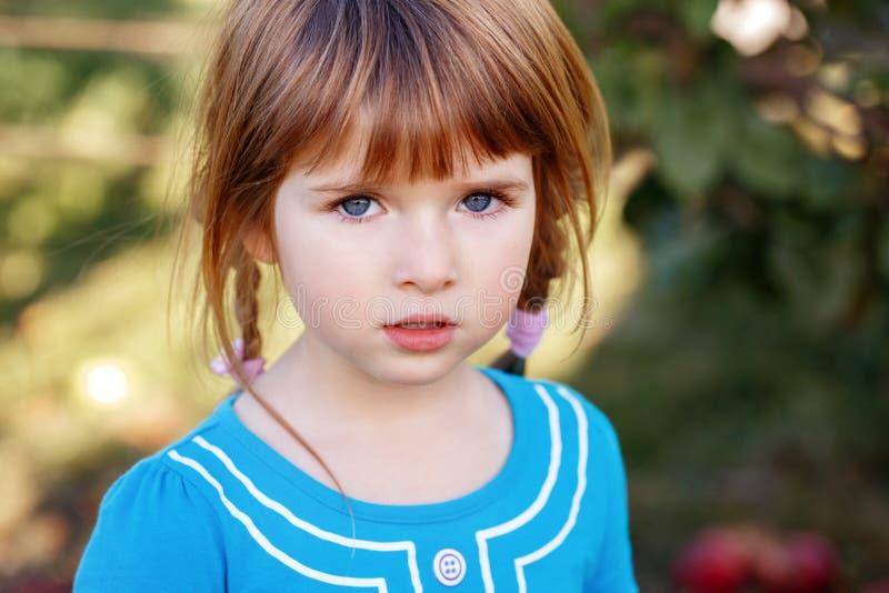 Close-upportret van leuke aanbiddelijk weinig roodharig Kaukasisch meisjeskind met blauwe ogen stock fotografie