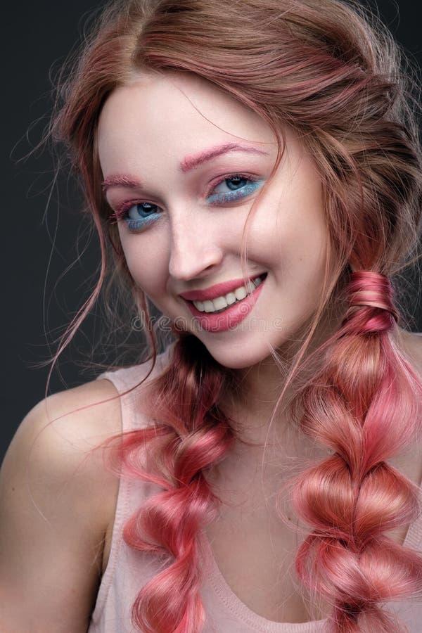 Close-upportret van meisje met roze haar in vlechten, roze en blauwe make-up Meisje die zich op een donkere achtergrond bevinden, stock foto