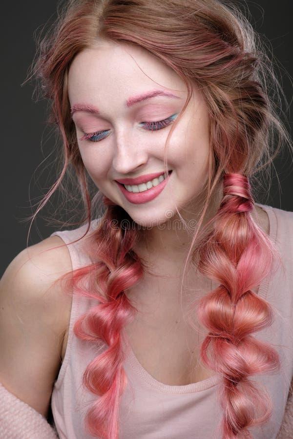 Close-upportret van meisje met roze haar in vlechten, roze en blauwe make-up Meisje die zich op een donkere achtergrond, gesloten royalty-vrije stock afbeelding