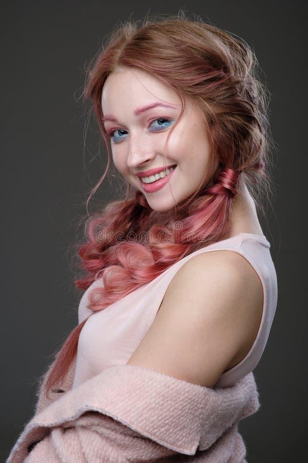 Close-upportret van meisje met roze haar in vlechten, en roze-blauwe make-up met een roze laag versleten van de schouder die zich royalty-vrije stock foto