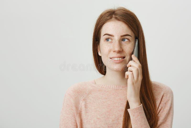 Close-upportret van mooi de holdingsgadget van de roodharigevrouw dichtbij oor, wachten voor somebody om telefoon op te nemen, di stock foto's