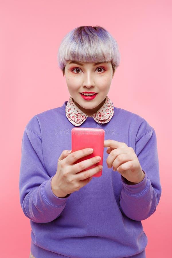 Close-upportret van mooi dollishmeisje met kort licht violet haar die lilac sweater dragen die selfie over roze maken royalty-vrije stock fotografie