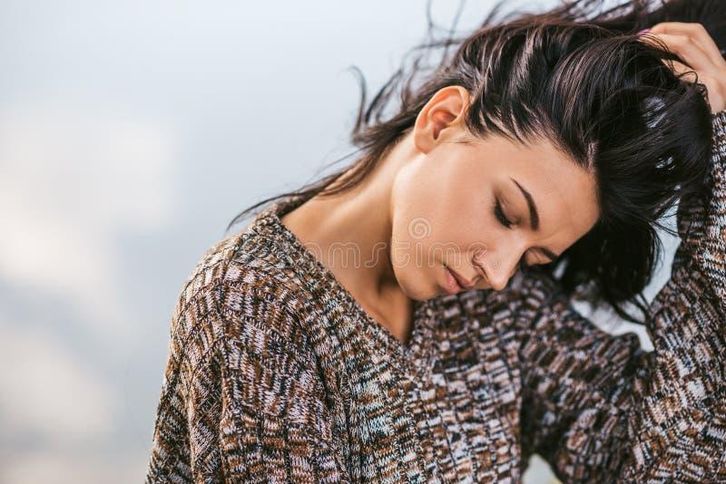 Close-upportret van mooi dromerig donkerbruin wijfje met gesloten ogen die tegen meer met blazend haar stellen Mensen, levensstij stock foto's