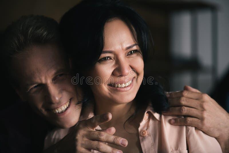 close-upportret van mooi gelukkig multi-etnisch paar die weg terwijl mens kijken royalty-vrije stock afbeelding