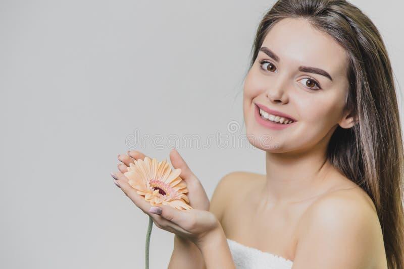 Close-upportret van mooi jong meisje op witte achtergrond met bloem in handen stock afbeeldingen