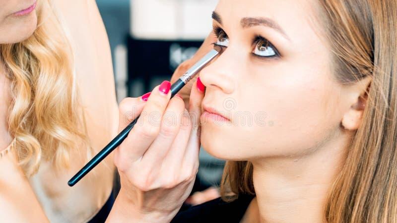 Close-upportret van mooi jong model met bruine ogen die terwijl make-upkunstenaar die met haar gezicht werken stellen stock foto's