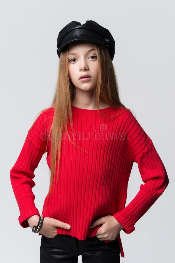 Close-upportret van mooi jong roodharigemeisje die het rode sweater stellen in studio dragen royalty-vrije stock afbeelding