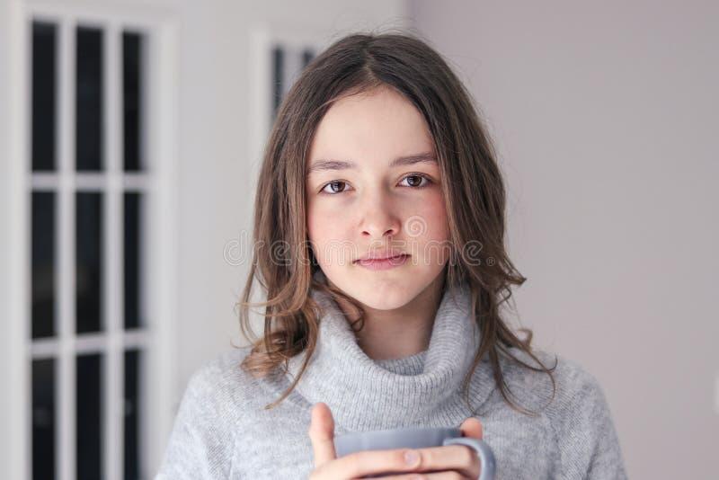 Close-upportret van mooi tween meisje die in de warme grijze kop thee van de truiholding camera bekijken stock foto