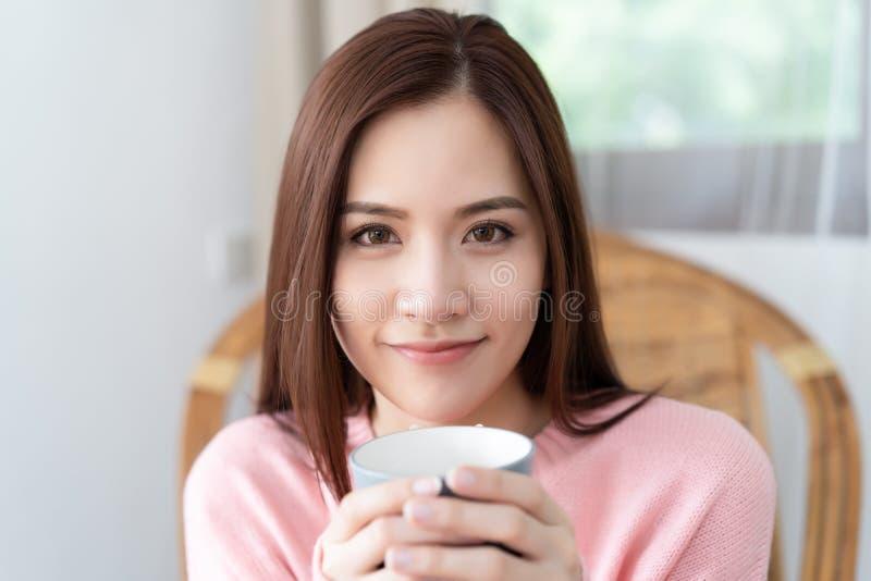 Close-upportret van mooie Aziatische vrouw die gebreid sweaterroze draagt terwijl het houden van kop van koffie en het bekijken c stock foto