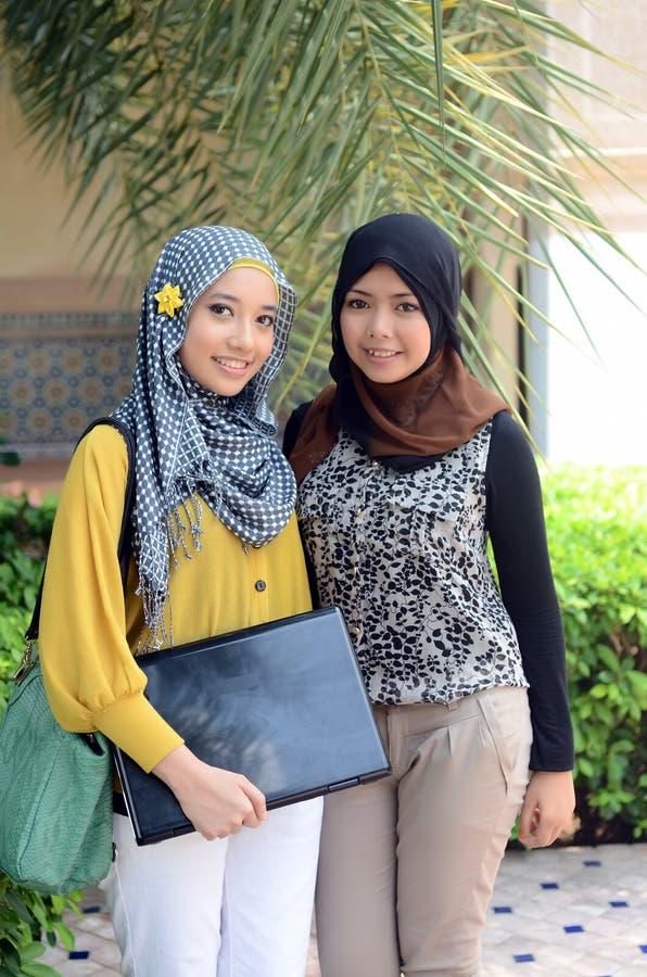 Close-upportret van mooie jonge Aziatische student met laptop stock foto