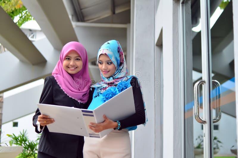 Close-upportret van mooie jonge Aziatische studentenstudie samen stock afbeelding
