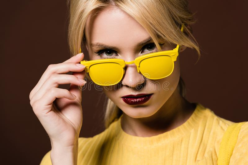 close-upportret van mooie jonge blondevrouw die in gele zonnebril camera bekijken stock afbeelding