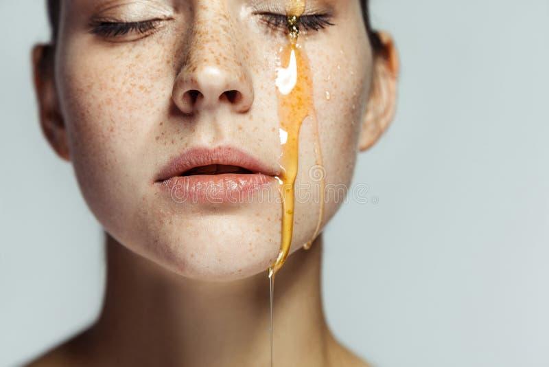 Close-upportret van mooie jonge donkerbruine vrouw met sproeten en honing op gezicht met gesloten ogen en ernstig gezicht stock fotografie