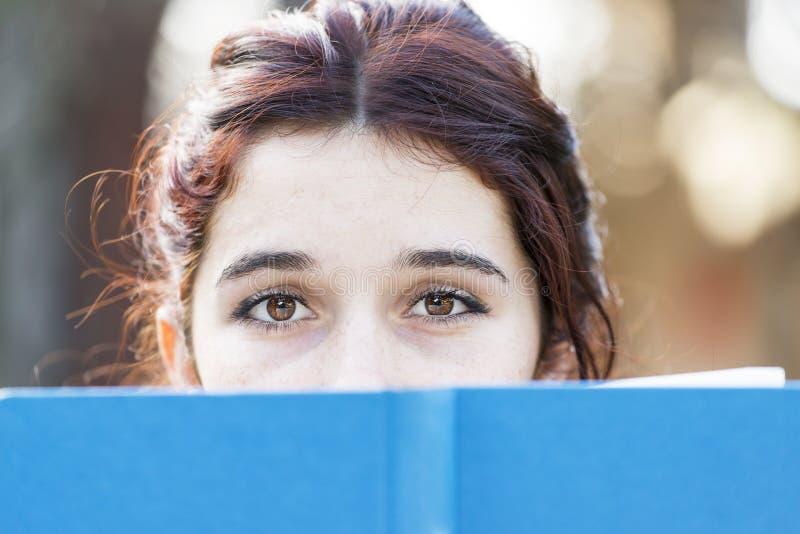Close-upportret van mooie Kaukasische vrouw met blauw boek stock foto's