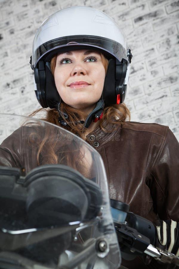 Close-upportret van mooie motorrijder in open helmzitting op de motor stock foto's