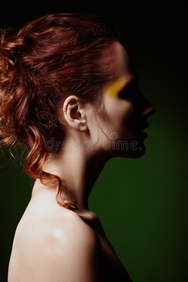 Close-upportret van mooie roodharige vrouw De mening van het profiel stock fotografie