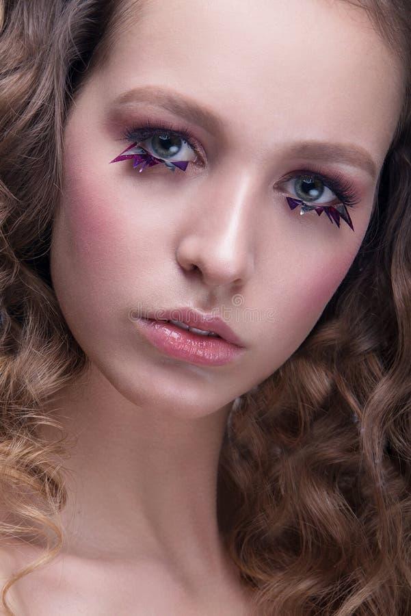 Close-upportret van mooie vrouw met heldere make-up en golvend kapsel Polijst manier glanzende highlighter op huid, lippenmake-up royalty-vrije stock fotografie