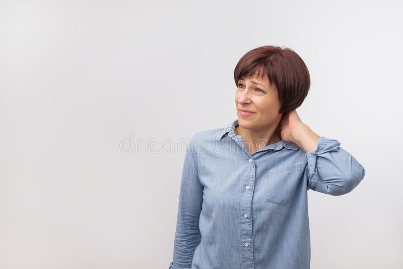 Close-upportret van ongerust gemaakte rijpe knappe vrouw status op grijze muurachtergrond met exemplaarruimte stock foto's