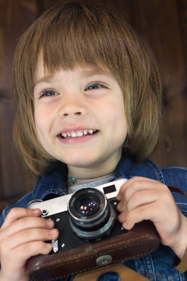 Close-upportret van ontzagwekkend glimlachend weinig jongen vier jaar oud met uitstekende filmcamera stock foto's