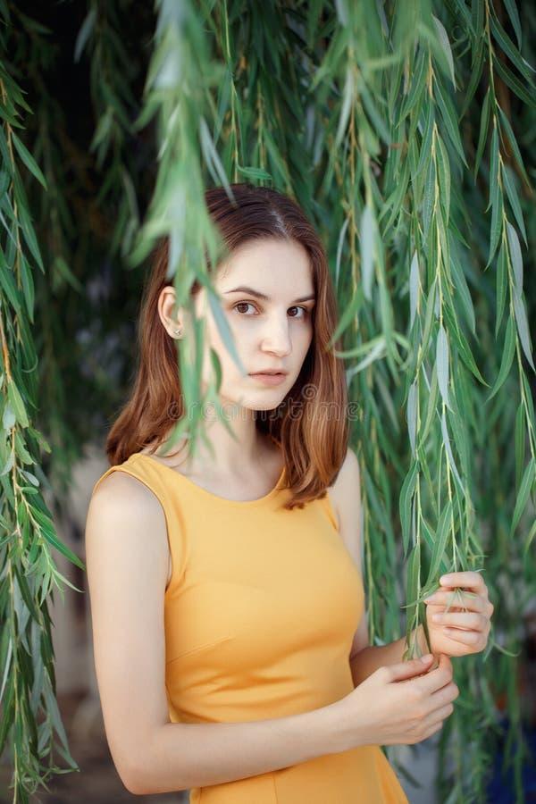Close-upportret van peinzend droevig mooi jong Kaukasisch vrouwenmeisje in gele kleding met rood haar, bruine ogen, die in camera stock foto's
