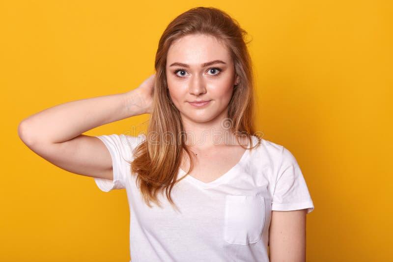 Close-upportret van positieve energieke jonge dame die wat betreft haar haar met één hand, direct camera bekijken, die prettig he royalty-vrije stock foto's